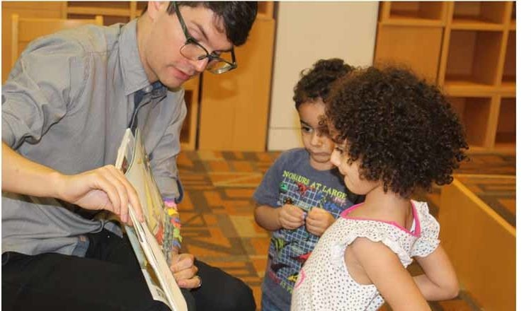 Man showing a book to children. (Photo Credit: State Department)