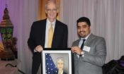 Two men holding a painting. (Photo Credit: State Department)